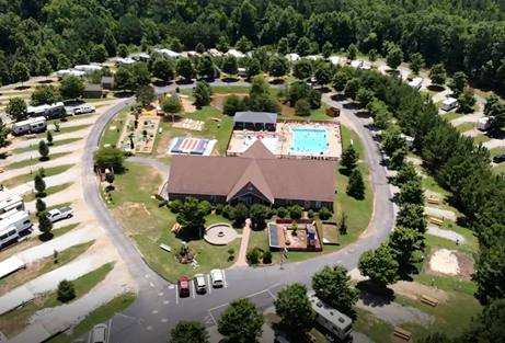 A large RV park with lots of trees, along with a large cabin and pool displayed in the middle